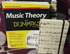 A picture of the book, Music Theory for Dummies and a note book with music notes on the cover